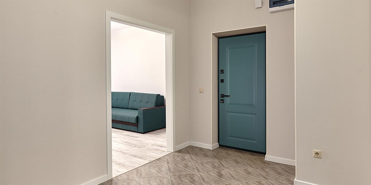 Яркая входная дверь в квартиру с черной фурнитурой